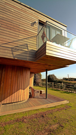Curved timber cladding on lower floor