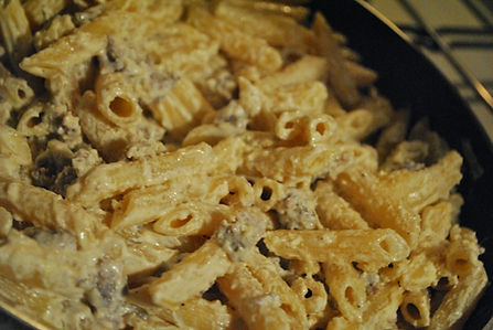 Stirring the Parmigiano Reggiano into the Penne alla Norcina Recipe