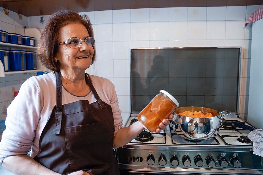Jamileh holding her pumpkin preserves in a mason jar, beirut, lebanon