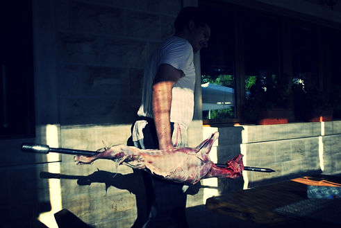 Chef Ivan carrying lamb on spit Konoba Kopačina, Island of Brač off the coast of Croatia