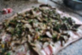 Adding the liver and fennel stuffing to the butterflied pancetta - Porchetta Ripiena aka Stuffed Pork Recipe
