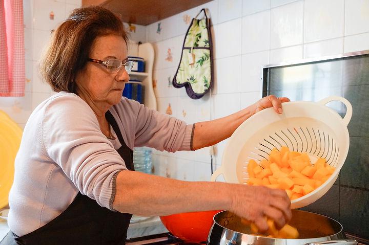 Jamileh adding the pumpkin to the boiling syrup, carmelized pumpkin recipe, Lebanon