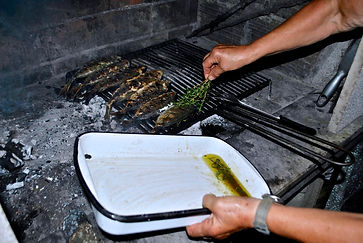 Domina adding sauce with rosemary twigs in Traditional Wood Fired Oven in Supetar, Brač, Croatia
