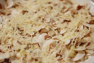Sprinkling the Parmigiano Reggiano over the sliced mushroom caps, White Mushroom Arugula Salad Recipe