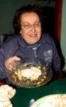 Amal smiling holding a plate of molokhia
