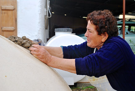 Covering up the chimney of the clay oven with mud