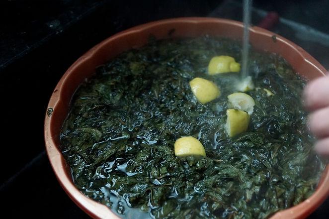 adding hot lemon water to molokhia leaves, molokhia recipe, lebanese recipes