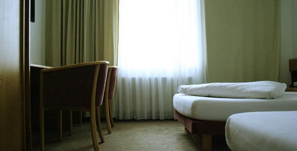 Gemütliches Zweibettzimmer mit großen Fenstern und Blick auf das Marchfeld.