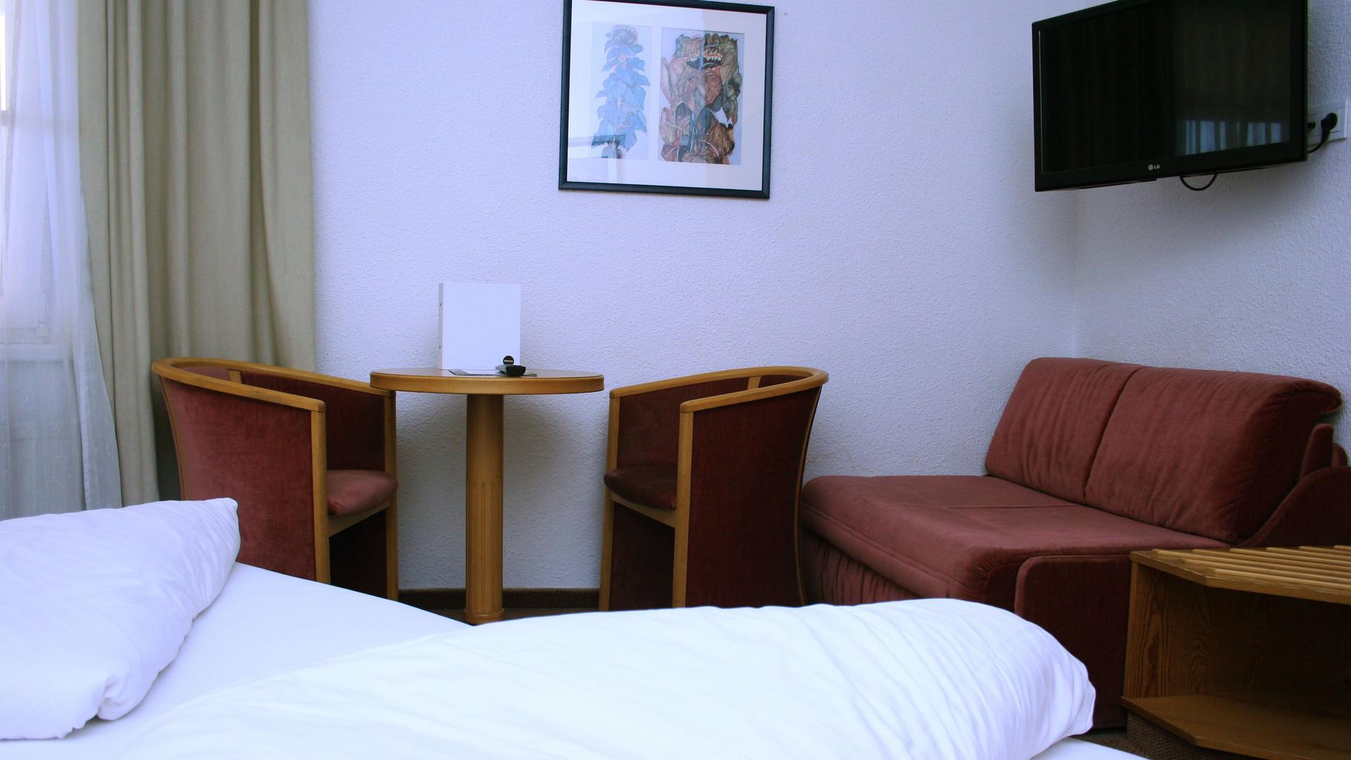 Geräumiges Doppelzimmer mit Couch und Fernseher im Hotel-Garni in Groß-Enzersdorf.