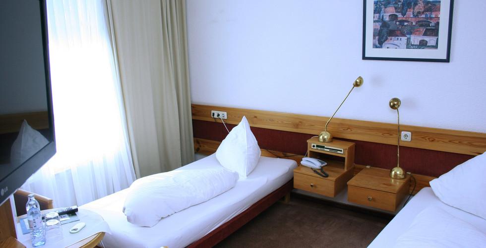 Großes Doppelzimmer mit Fernseher und großen Fenstern bei angenehmer Morgensonne.
