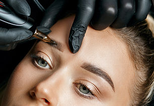 Cosmetician doing eyebrow tattooing on a female brows. Closeup shot_.jpg
