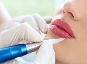 Young woman having permanent makeup on lips in beautician salon.jpg