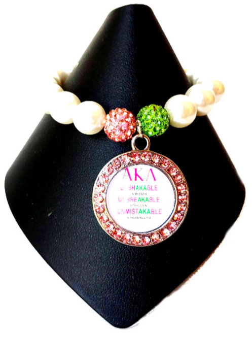 White pearls, one green and pink bead, pendant outlined in pink crystals, lettering in pink and green,