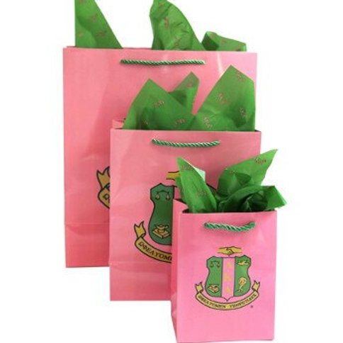 Front view of package. Pink bags and tissue paper. Shield on front in green and pink.