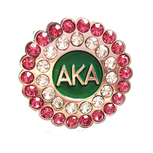 Outlined in pink crystals, next row clear crystals, inner circle green with gold AKA letters.