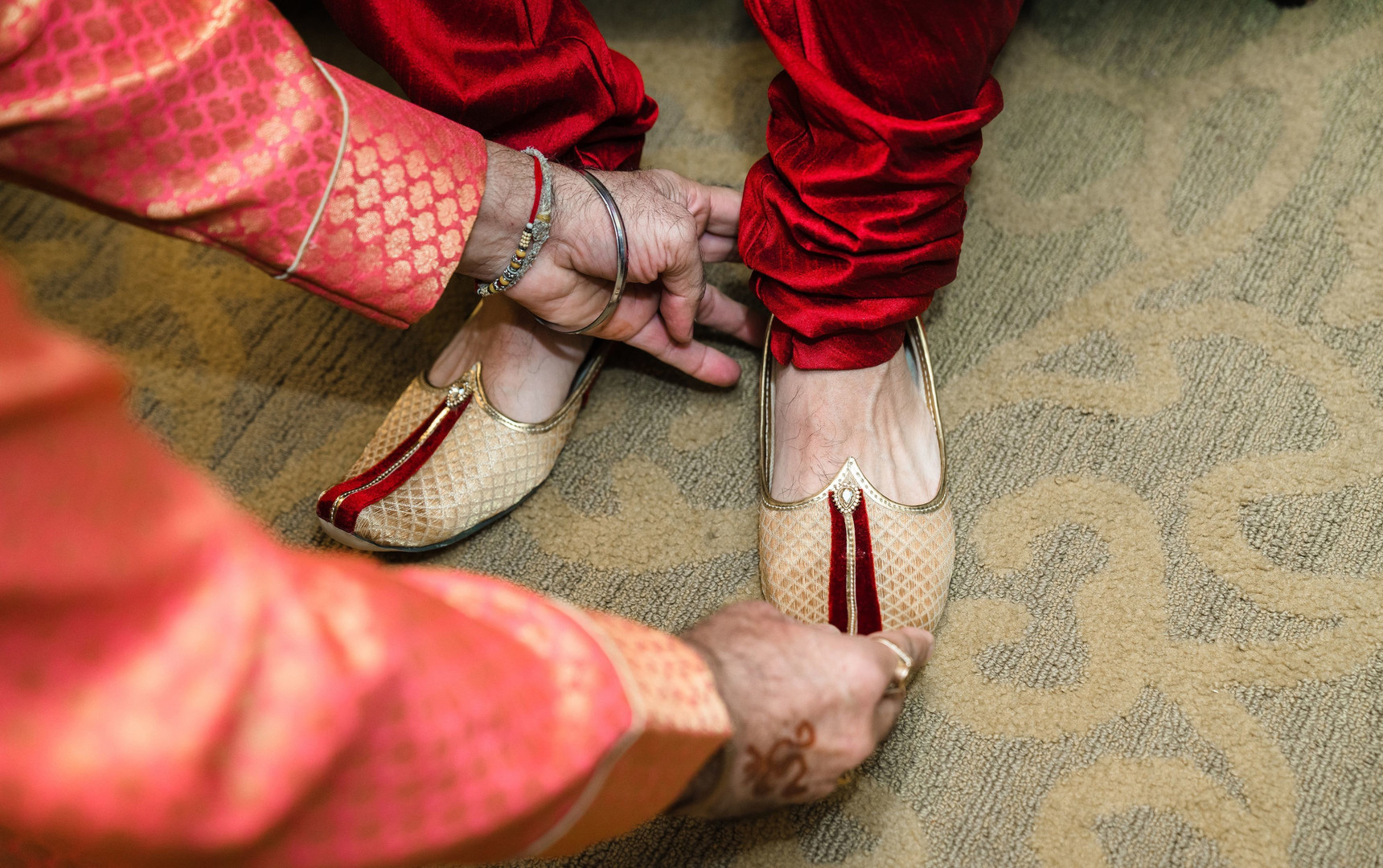 Indian groom being assisted to put his e