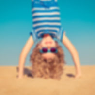 Funny child standing upside down on sand