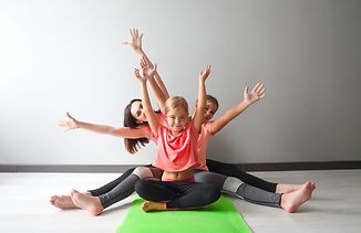 Young woman having fun with kids doing yoga. Family sport concept.jpg