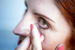 young woman putting contact in eye.jpg