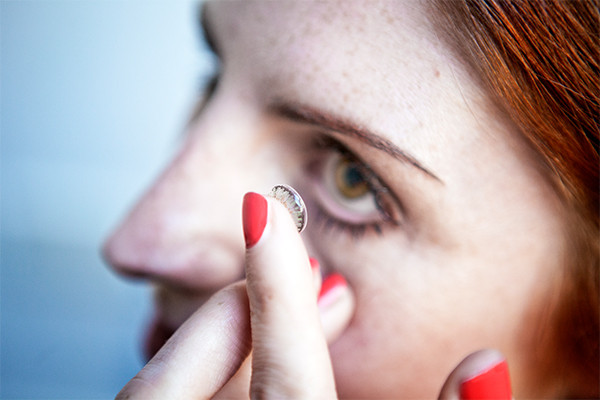 Women putting a contact lens in her eyes