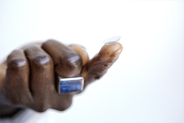 Man with a contact lens on his finger