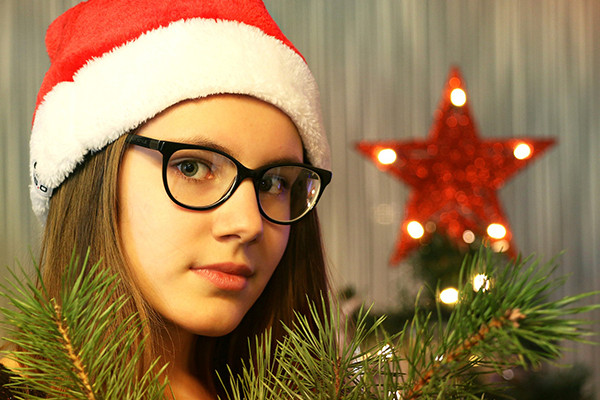 Teenager wearing spectacles in front of Christmas tree