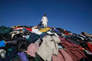 A man stands on top of a pile of used jackets for sale along a road in Quetta October 17, 2011. REUTERS/Naseer Ahmed (PAKISTAN - Tags: SOCIETY BUSINESS EMPLOYMENT TPX IMAGES OF THE DAY)