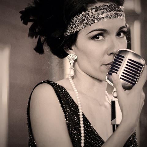 Vintage Jazz Singer, Jackie Lopez, singing Frank Sinatra songs behind the mic.