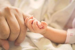 赤ちゃんは親の小指の指を保持します