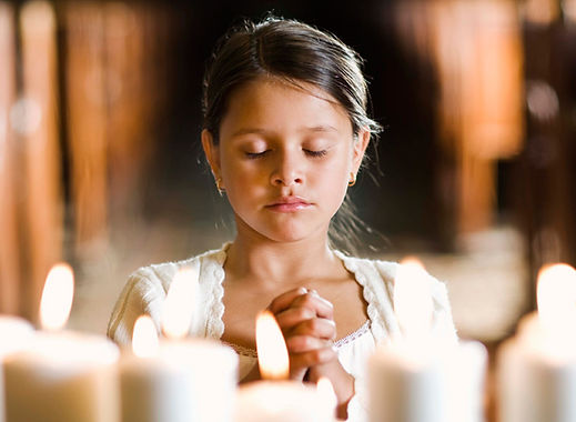 An obedient child in prayer before a menorah