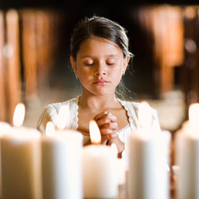 dziwczynka modli się podcas pierwszej komunii świętej