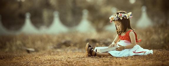 Meisje leest boek in een weiland met een bloemenkrans om haar hoofd