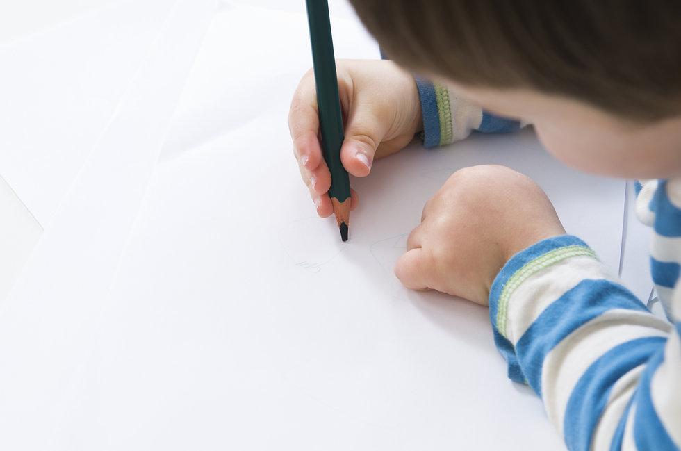 Jongentje tekent met een potlood in een schrift