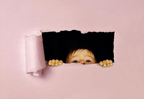 Kind kijkt door een scheur in de muur