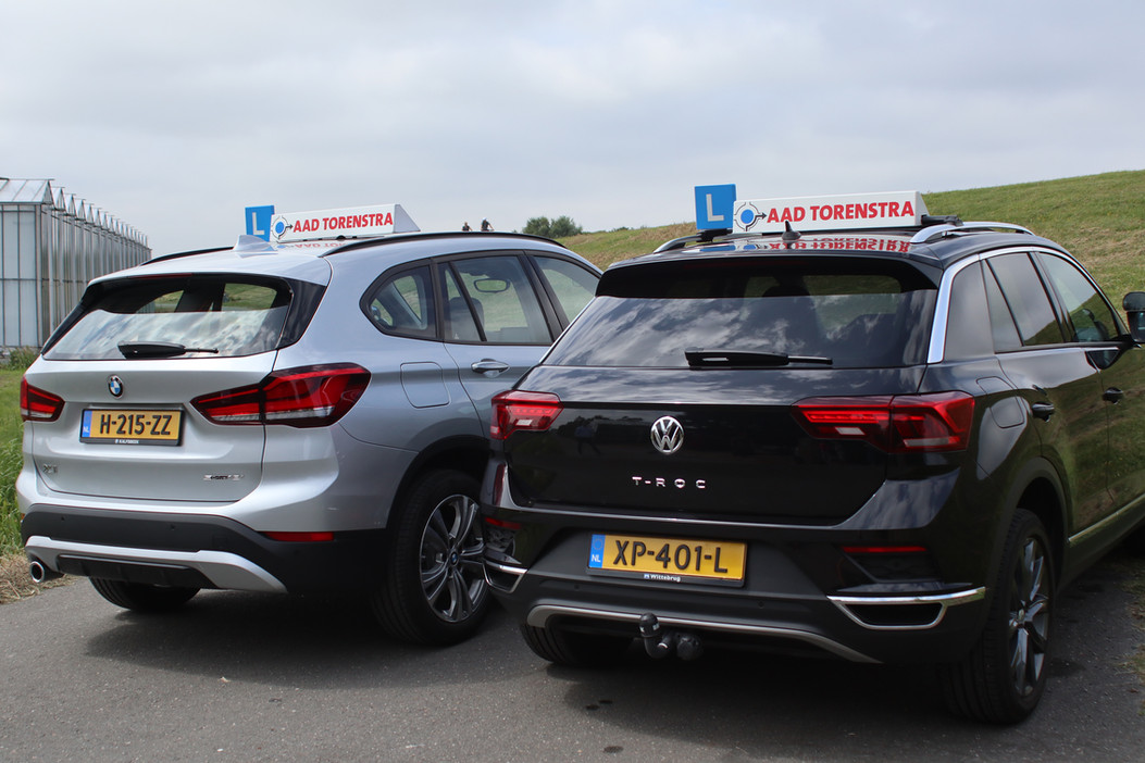De BMW X1 en de Volkswagen T-Roc waarin autorijlessen worden gegeven bij Autorijschool Torenstra van achteren gezien