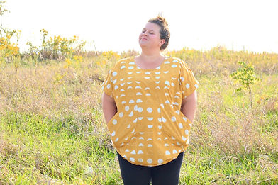 Smiling plus size woman standing in a naturalized field, with her hands in her oversized decorative tunicpockets