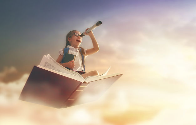 Back to school! Happy cute industrious child flying on the book on background of sunset sk