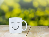 Smiley coffee cup on wood table with gre