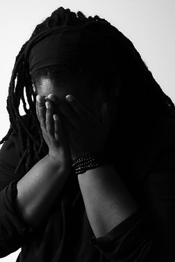 Ashley Lumpkin, a Black woman is pictured in black and white. Her head is down, and her face is obscured by both hands. A strand of beads is wrapped around her wrist.