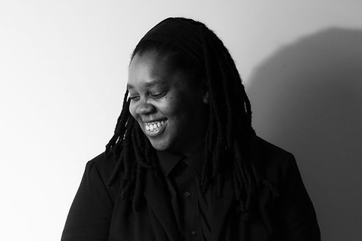 Ashley Lumpkin, a Black woman wearing a blazer and button down shirt, is pictured in black and white. Her face is pointed down and to the right, with her eyes closed. She has a wide smile. A shadow is cast behind her.