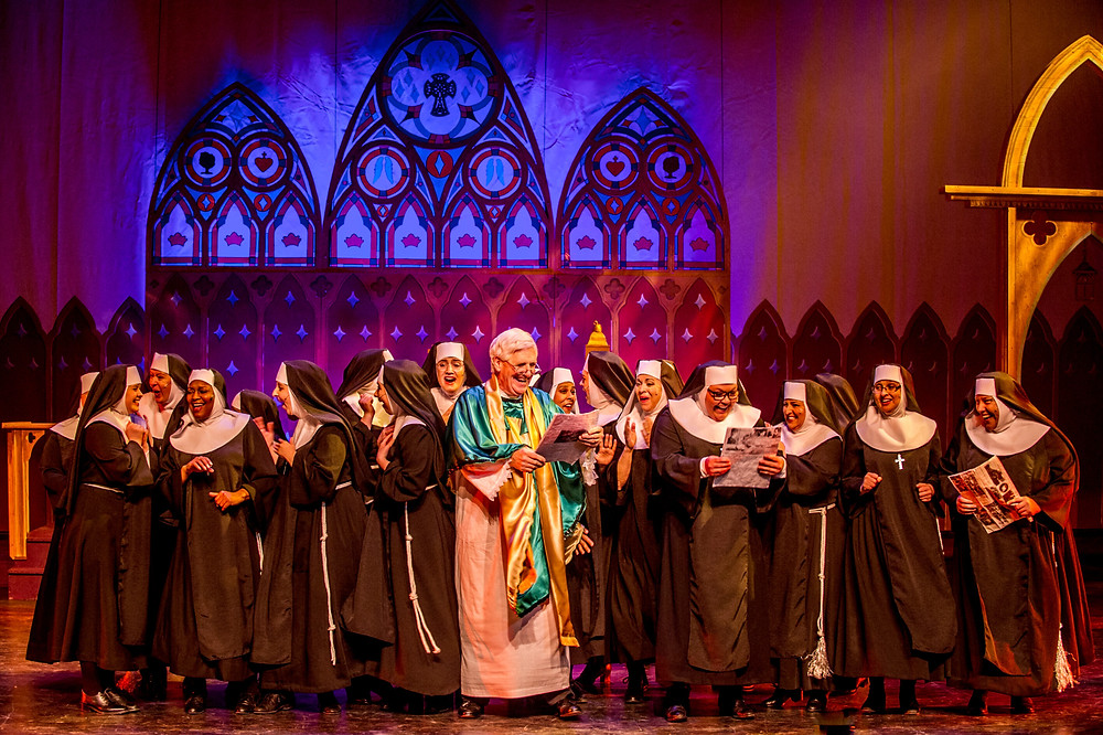 Assembled nuns of the Queen of Angels church with Monsignor O'Hara celebrating reviews in the paper