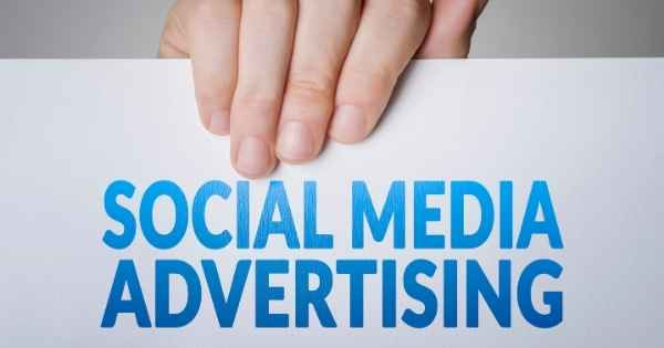 Hand holding sign that says social media advertising