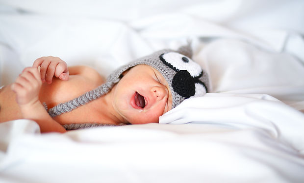 A Cute Sleeping Baby on a Fluffy White Dovet