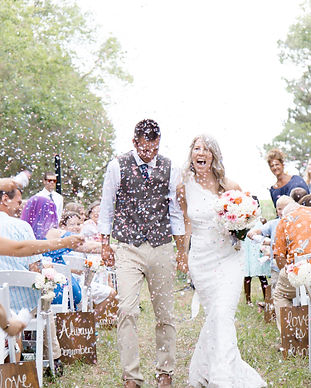 Couple on their wedding day celebrating on the way down the aisle with confetti