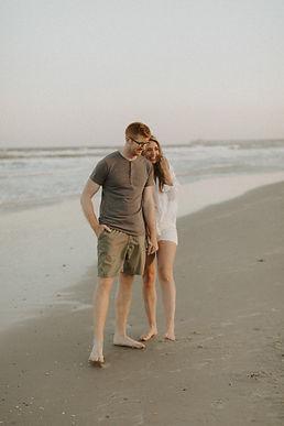 Image of couple, in South Carolina beach laughing & walking