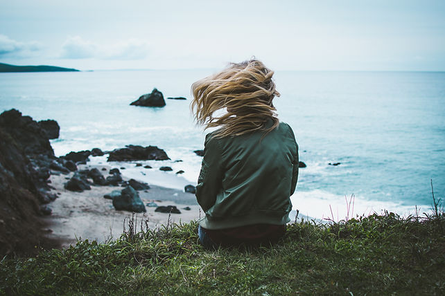 girl sitting on a cliff overlooking the