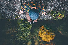 Man Traveler sitting on cliff bridge edg