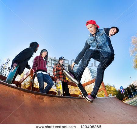 skateboarder-with-friends-in-skatepark-jumping-in-the-halfpipe-129496265.jpg