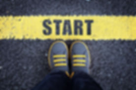 Start line child in sneakers standing next to a yellow starting line.jpg
