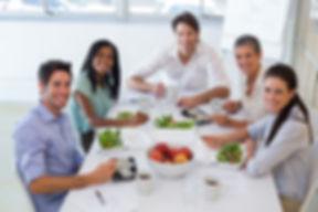 Workers smile at camera while eating healthy lunch in the office.jpg